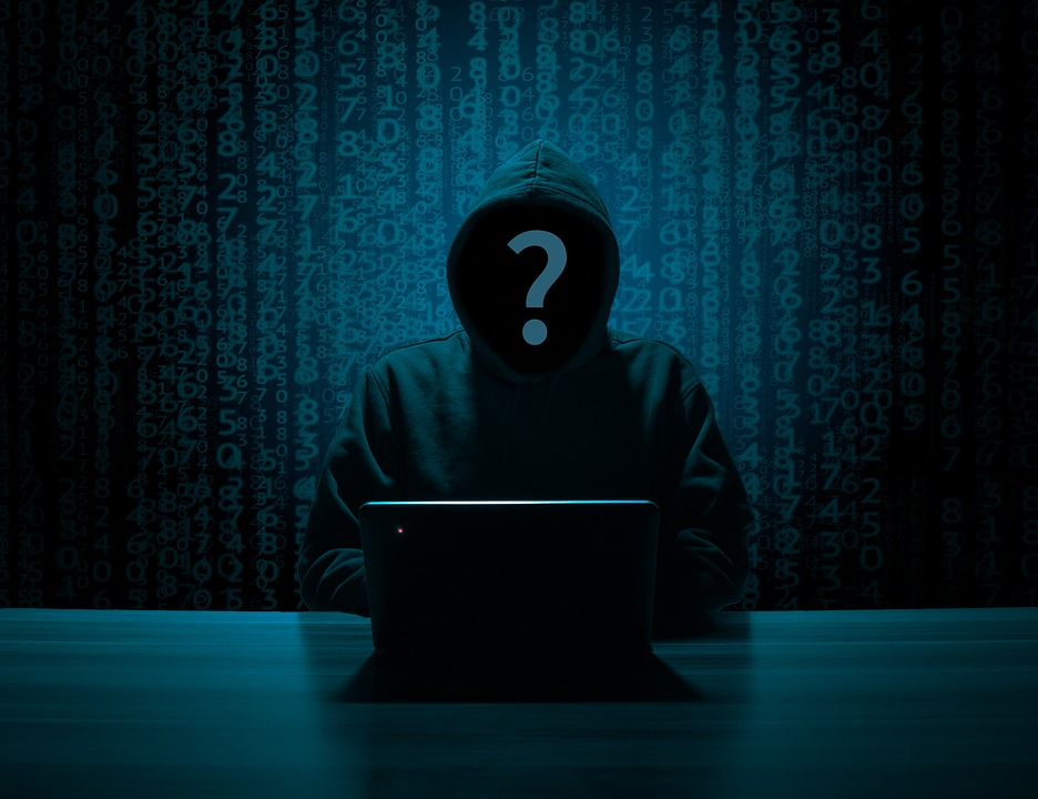 Cybercriminal in a black hoodie hacking company networks to perform a data breach.