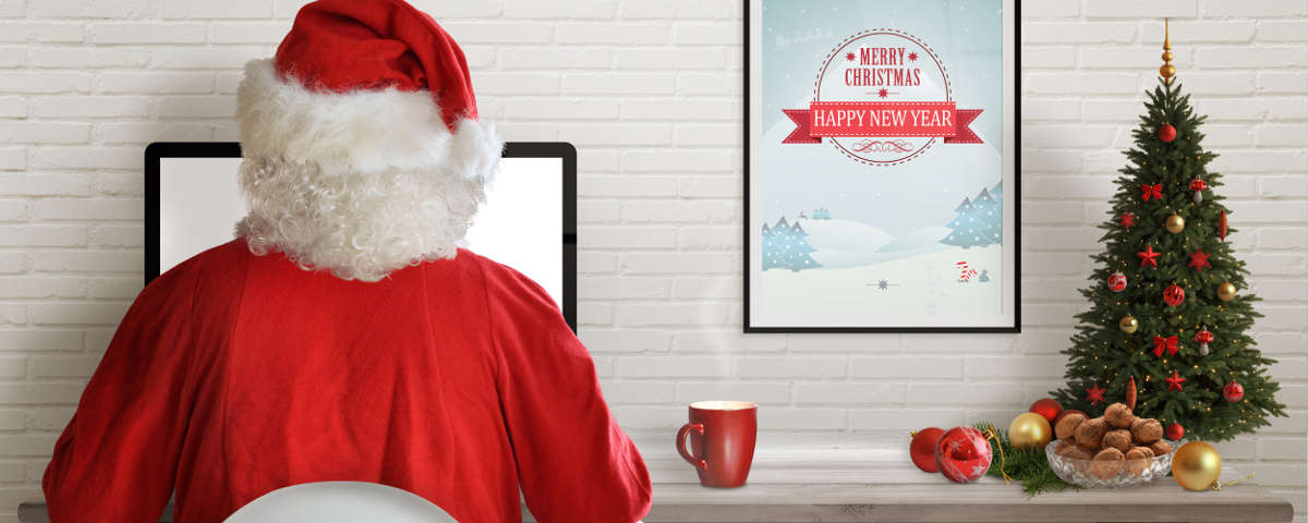 Santa Clause on a desktop computer reviewing employee productivity reports.