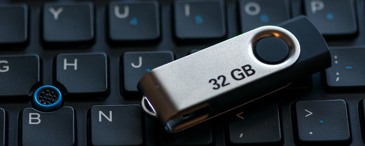 A 32 gigabyte USB flash drive sitting on top of a computer keyboard